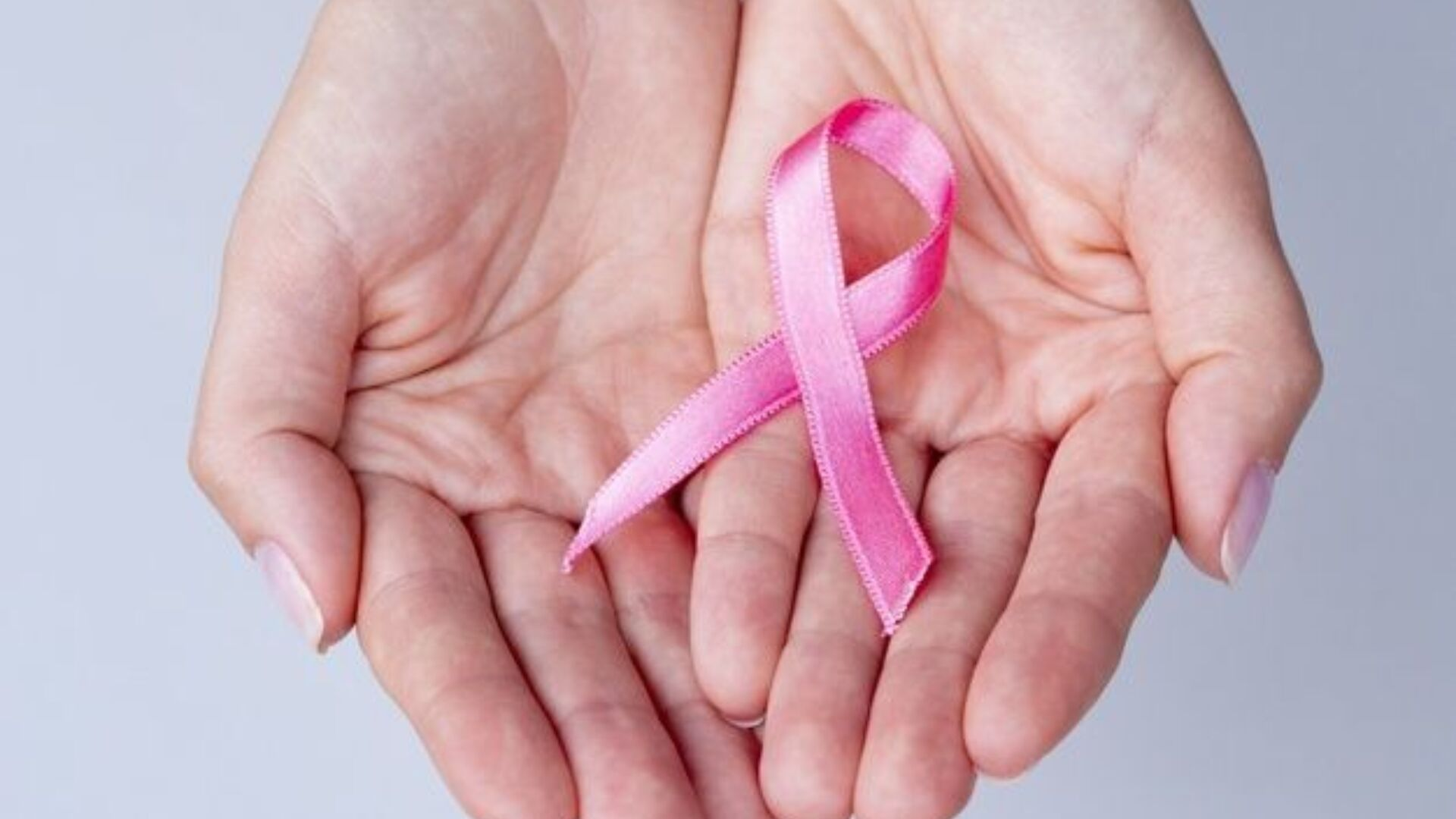 Download Close up Hands Holding Pink Ribbon for free